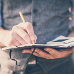 close up hands man writing on diary and smartphone