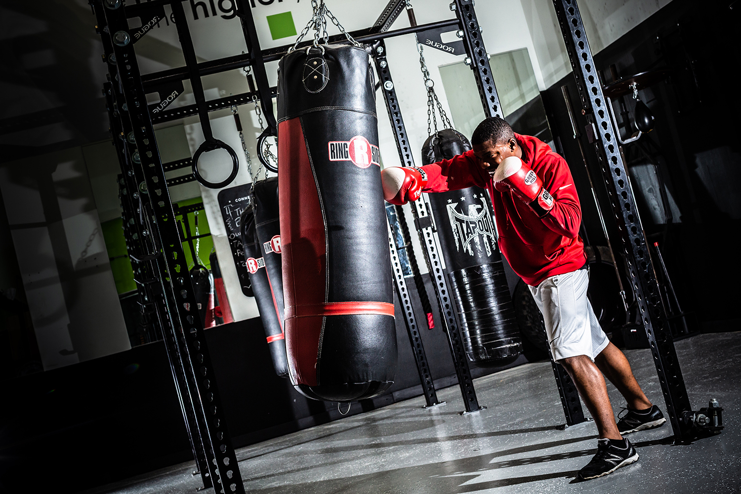 Man in red hoodie punching bag
