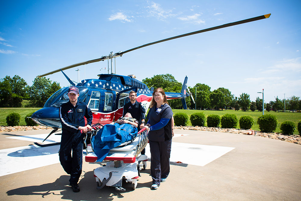 medical providers pushing patient away from helicopter