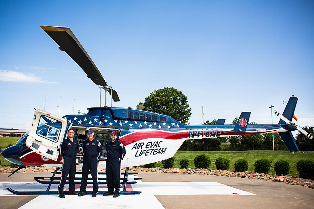 three pilots in front of medical helicopter