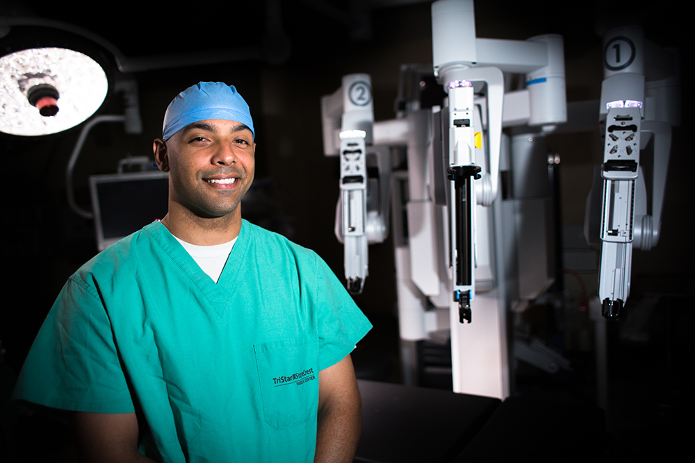 male surgeon in front of robot in surgical suite.