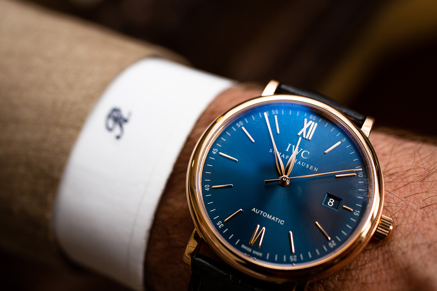 IWC blue faced watch on mans wrist.
