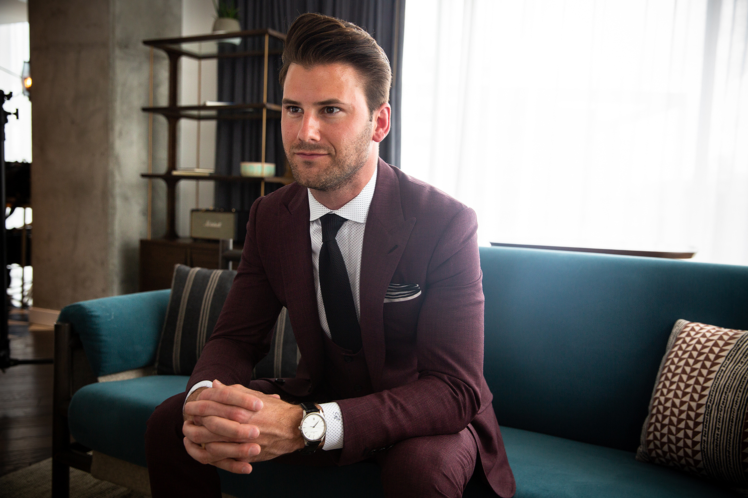 Stephen Richards of Richards Bespoke wearing a wine colored suit sitting at The Thompson Hotel Nashville.