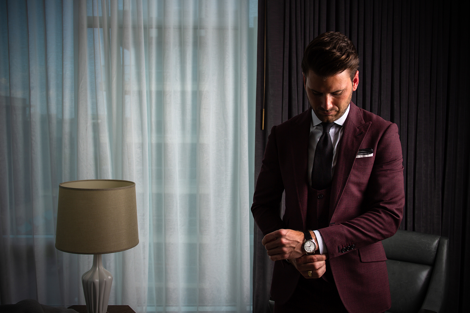 Man wearing a wine colored suit designed by Richards Bespoke at The Thompson Hotel Nashville.